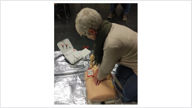 Den Sprachanweisungen des Defibrillators folgen, dann 2 Minuten Herzdruckmassage